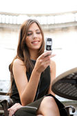 Beautiful businesswoman using a cell phone while sitting in a classic coffee shop — Stock Photo