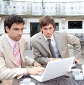 Portrait of two focused businessmen having a meeting in a coffee shop terrace — Stock Photo