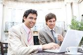 古典的なコーヒー ショップのテラスに座りながら会議を行っている 2 人のビジネスマン — ストック写真