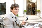 Mladá atraktivní podnikatel pomocí mobilního telefonu při posezení v kavárně hotelu — Stock fotografie