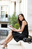 элегантные бизнесвумен, сидя на классических зданий шаги заметок — Стоковое фото