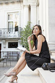 Attractive businesswoman being thoughtful while sitting in a colonial building's stairs — Stock Photo