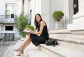 メモを取って古典的な建物のステップの上に座ってエレガントな実業家 — ストック写真