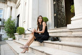 Elegant businesswoman sitting on a classic buildings steps taking notes in her agenda — Stock Photo