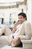 Unga attraktiva affärsman leende och med en mobiltelefon — Stockfoto
