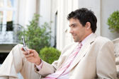 Attractive businessman using his cell phone while sitting on the steps — Stockfoto