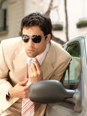 Attractive businessman grooming himself using a car mirror outdoors — Stok fotoğraf