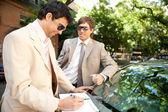 Dos empresarios trabajando mientras se apoyaba en un coche de lujo en una calle arbolada de la ciudad. — Foto de Stock