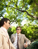 Two businessmen having a conversation while leaning on a car — Stock Photo