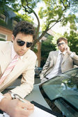 Two attractive businessmen meeting in a tree lined street — Stock Photo