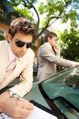 Hombres de negocios atractivas trabajando juntos al aire libre mientras se apoyaba en un coche de lujo — Foto de Stock