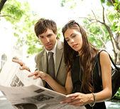 Mladá atraktivní podnikatel a podnikatelka stáli a sdílení noviny — Stock fotografie