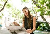 Schöne junge geschäftsfrau, lesen eine zeitung und stützte sich auf ein auto — Stockfoto