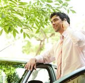 Attractive businessman with his car having a phone conversation using a hands free set — Stock Photo
