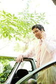 Young attractive businessman with his car having a phone conversation using a hands free set — Stock Photo