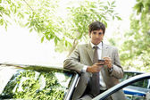 Attractive businessman leaning on a car's top while using a smart phone — Stock Photo