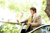 Attractive young businessman using a smart phone while leaning on the door of his car — Stock Photo