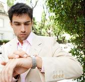 Jeune homme d'affaires attrayant en regardant l'heure à sa montre — Photo