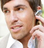Attractive young businessman using a hands free ear piece device to make a phone call — Stock Photo