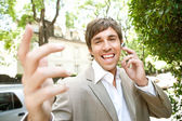 Espressive young businessman using an ear piece device — Stock Photo