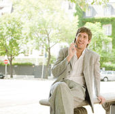 Businessman sitting on a bench in the financial district — Stock Photo