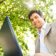 Attractive young businessman using a laptop pc computer — Stock Photo