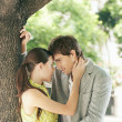 Young attractive business couple being affectionate to each other under a tree in the city. - Stock Photo