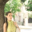 Young attractive professional businesswoman leaning on a tree trunk in the city. — Stok fotoğraf