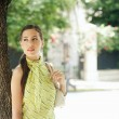 Attractive young businesswoman standing under a tree in the city — Stock Photo