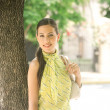 Young attractive businesswoman leaning on a tree trunk in the city - Stock Photo