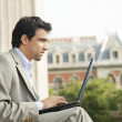 Young businessman sitting down with his laptop pc — Stock Photo