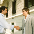 Stock Photo: Two businessmen shaking hands while standing outdoors