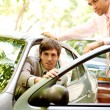 Two attractive businessmen with a smart car in a leafy street — Stock Photo #21930873