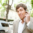 Stock Photo: Young businessmusing hands free ear piece device to make phone call