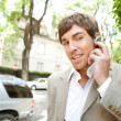 Young businessmusing hands free ear piece device to make phone call — Stock Photo #21930889