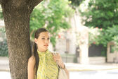 Young attractive professional businesswoman leaning on a tree trunk in the city. — Stock Photo