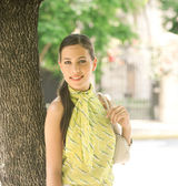 Young attractive businesswoman leaning on a tree trunk in the city — Stock Photo