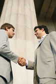 Two young businessmen shaking hands in agreement — Stockfoto