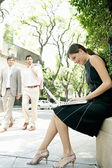 Two businessmen walking in the street and looking at a sexy businesswoman sitting down using her laptop computer. — Stock Photo