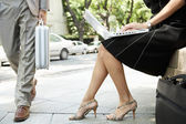Businessman walking passed a sexy businesswoman who's using her laptop computer — Stock Photo