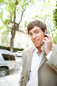 Young businessman using a hands free ear piece device to make a phone call — Stock Photo
