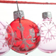 Small pink and red barballs Christmas tree ornaments hanging aligned on a red string - Stock Photo