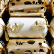 Three golden christmas crackers decorated with beads and ribbons - Stock Photo