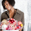 Young black woman holding a dish full of christmas barballs — Stockfoto