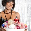 Attractive black woman holding a dish full of christmas barballs — Zdjęcie stockowe