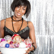 Attractive black woman holding a dish full of christmas barballs — Stock Photo #22106863