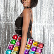 Young balck woman holding a box with different color christmass balls decorations - Stock Photo