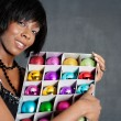 Attractive black woman holding a box full of various christmas barballs — Foto de Stock