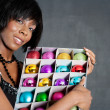 Attractive black woman holding a box full of various christmas barballs — Zdjęcie stockowe