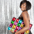 Young balck woman holding a box with different color christmass balls decorations — Foto de Stock